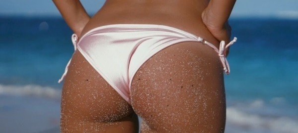 close-up of tanned bum in shiny pink bikiniwear