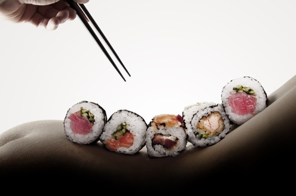 close-up of sushi on the lower back of a naked woman