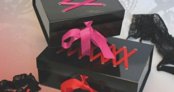 two black surprise boxes from sexstore with sexy gifts wrapped with pink and red ribbons