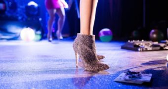 Legs of a woman wearing glittery boots at a party