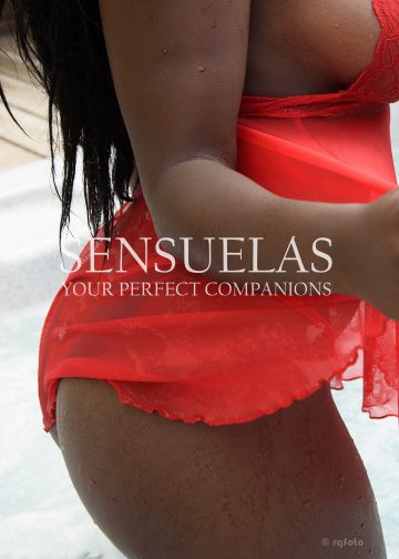 Sensuelas black companion Christina standing in a jacuzzi with her back to the camera wearing a red babydoll showing her bum close-up