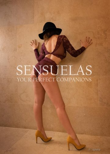 Sensuelas sexy escort model Stella standing against a wall wearing a fully lace top with sleeves and underwear and a black hat showing of her bum to the camera