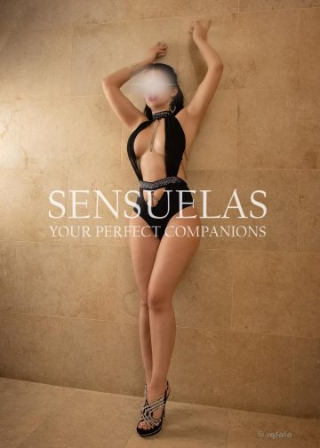 Sensuelas top companion Vanessa wearing a Black Lined Halter Open Side Middle Skinny DIP Monokini Bikini with strass and open high heels standing stretched against a wall facing the camera