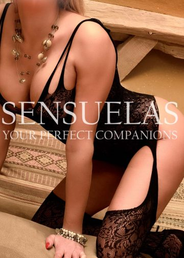 Blond Sensuelas escort model Sandra posing on hands and knees on a sofa wearing black see-through nylon body-stockings and black high heels