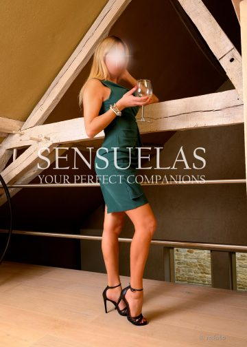 Blond Sensuelas escort model Sandra standing in a loft holding a glass of wine and wearing an elegant green dress and black high heels