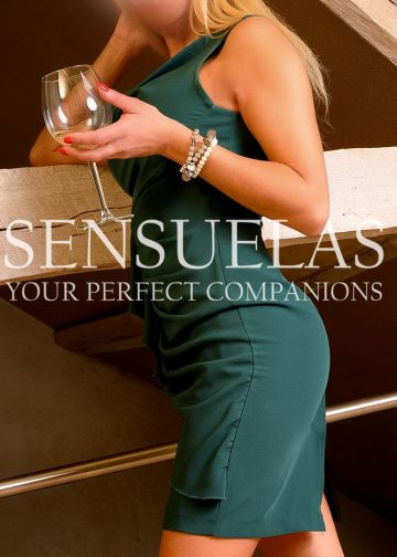Blond Sensuelas escort model Sandra standing in a loft holding a glass of wine and wearing an elegant green dress